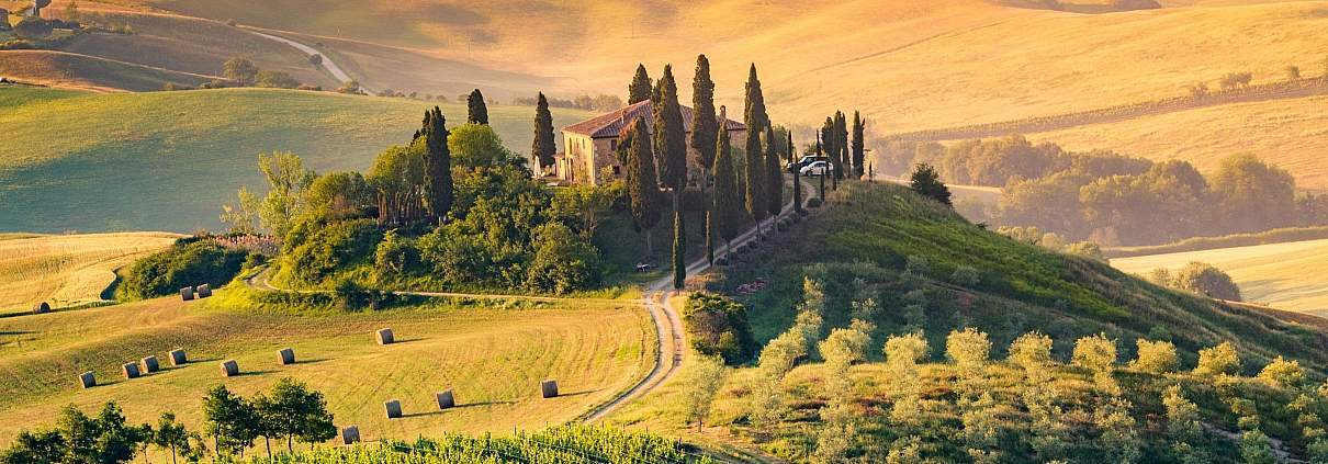 Rolling hills of Tuscany with cypress trees and a small town in morning mist.